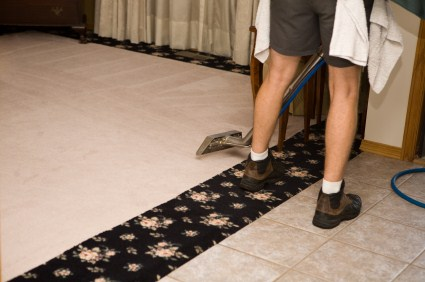 Viviane's Cleaning & Restoration Inc technician cleaning carpet via hot water extraction.